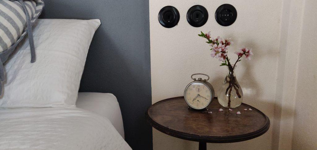 camera nei toni del grigio con comodino e sveglia antica