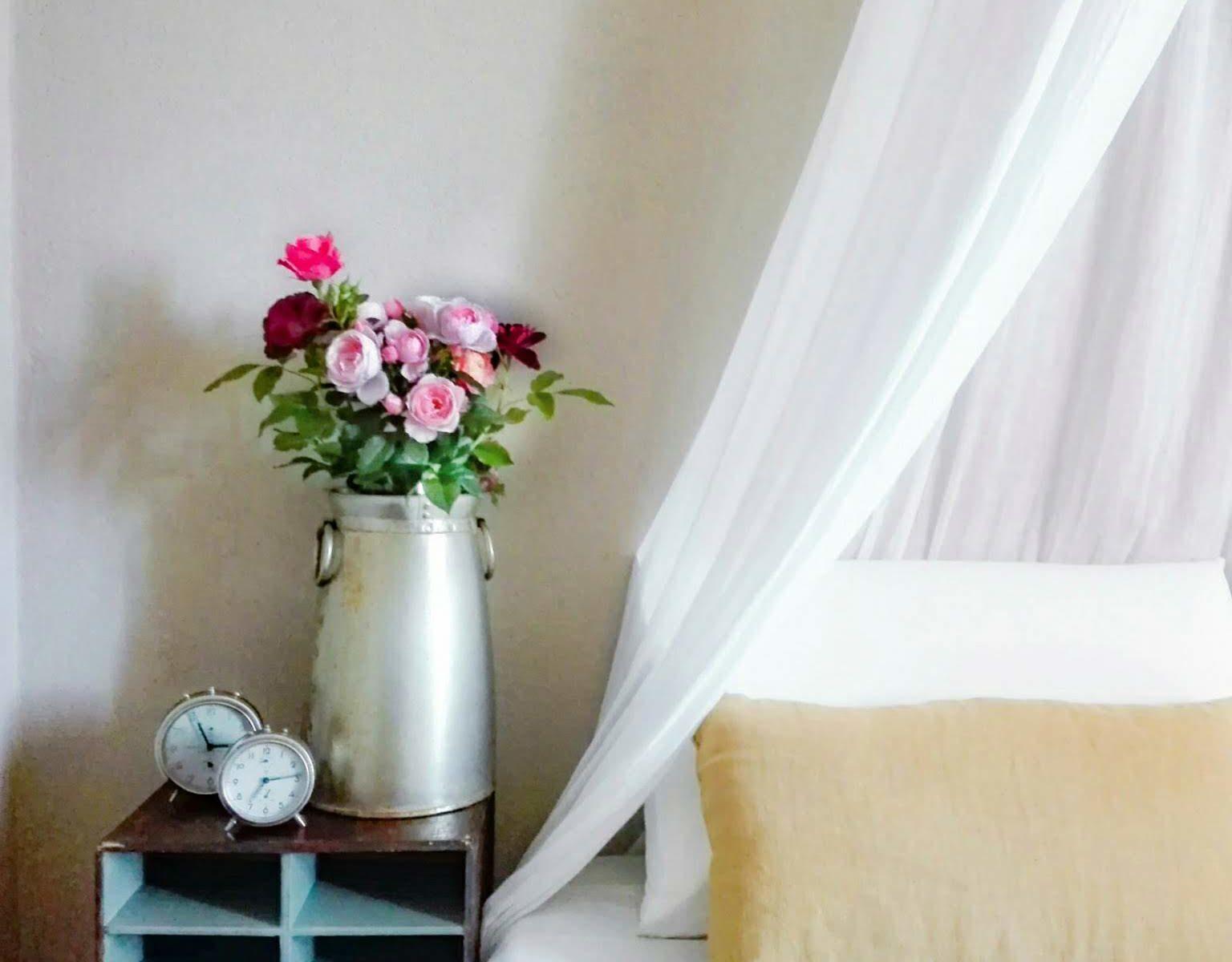 camera con letto a baldacchino e fiori sul comodino
