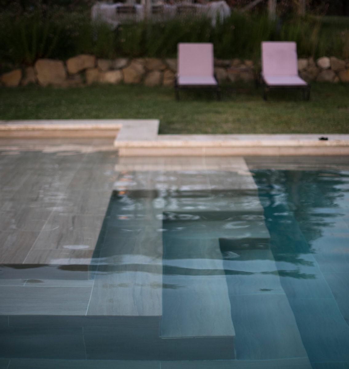 piscina al tramonto con tavola sullo sfondo